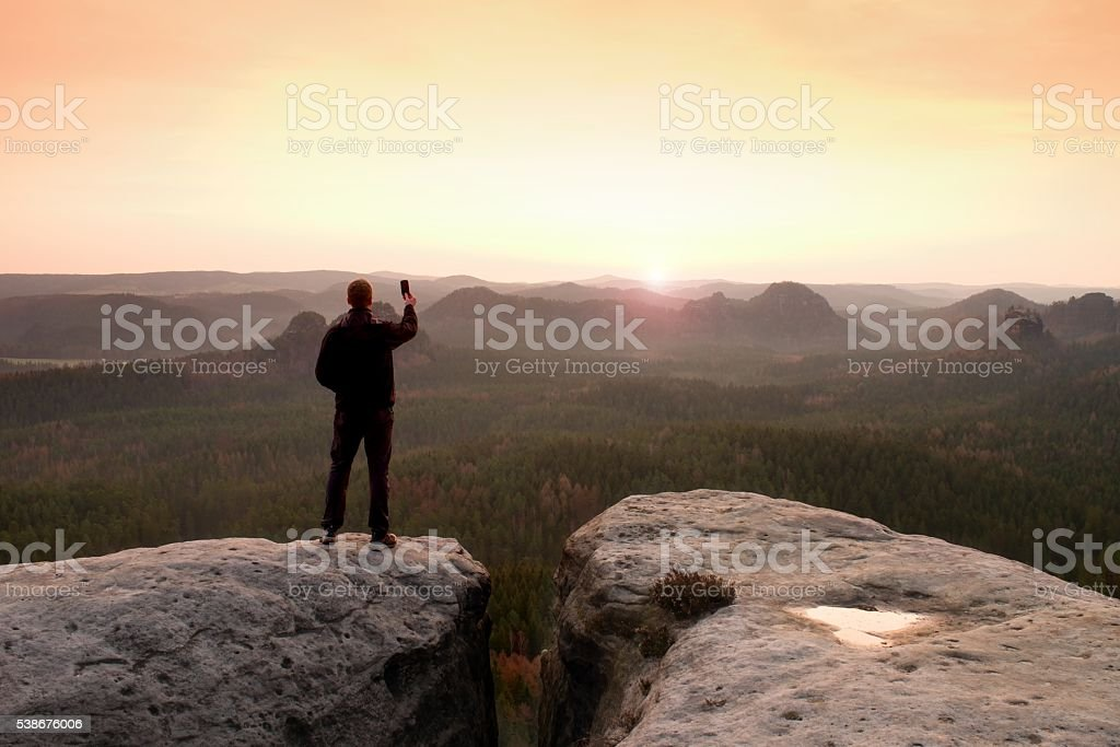Man photography with phoneof  dreamy hilly landscape stock photo