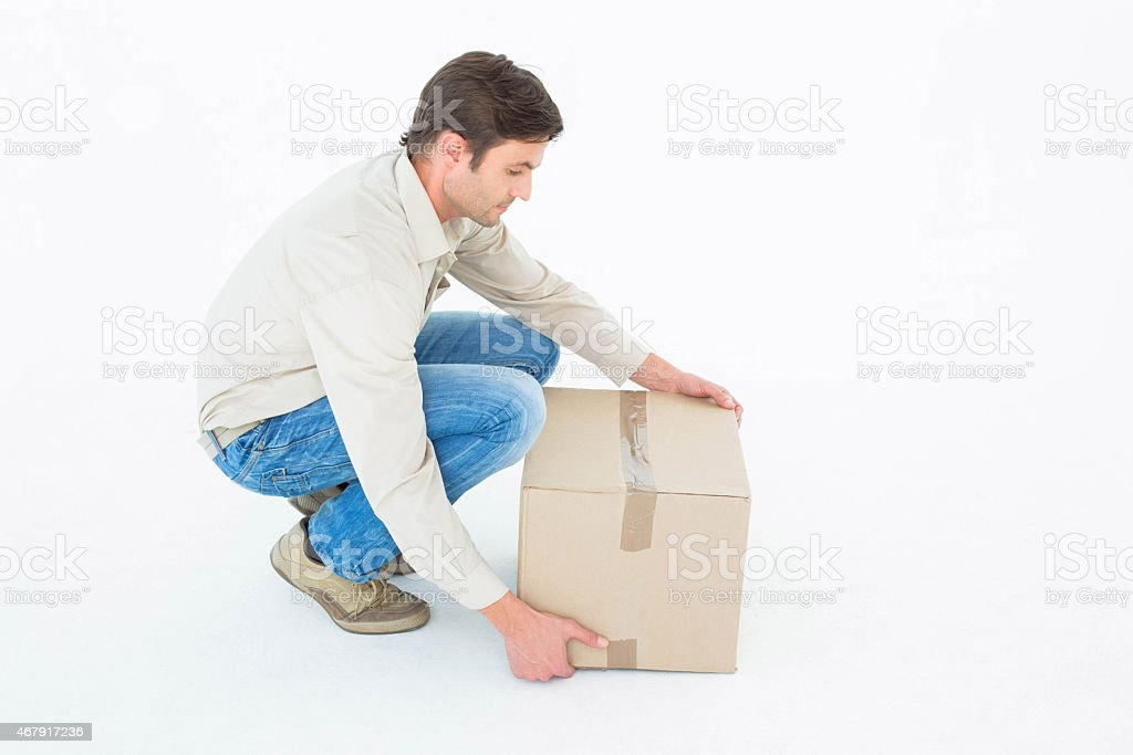 Man picking up a cardboard box off the ground stock photo