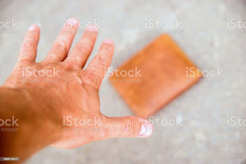 Man picking up lost wallet from ground stock photo