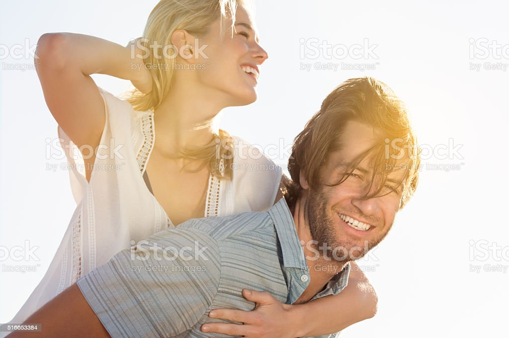 Man piggybacking woman stock photo