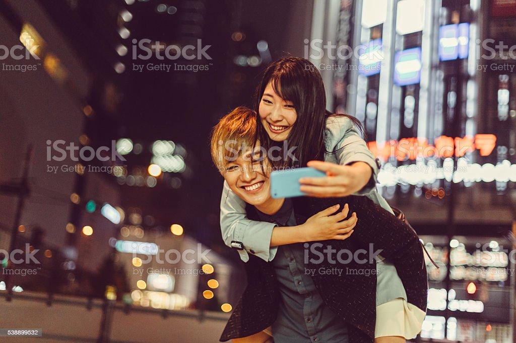 Man piggybacks girl for a selfie in Osaka stock photo