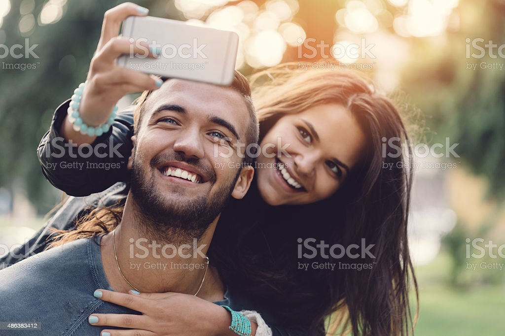 Man piggybacks girl for a selfie stock photo