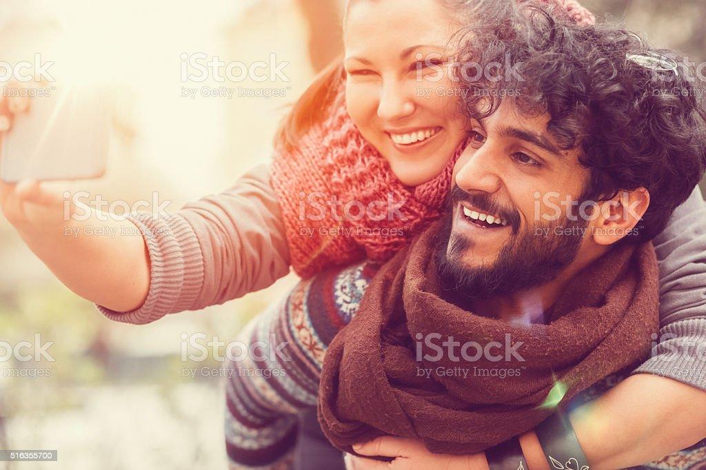 Man piggybacks girl for a selfie stock photo