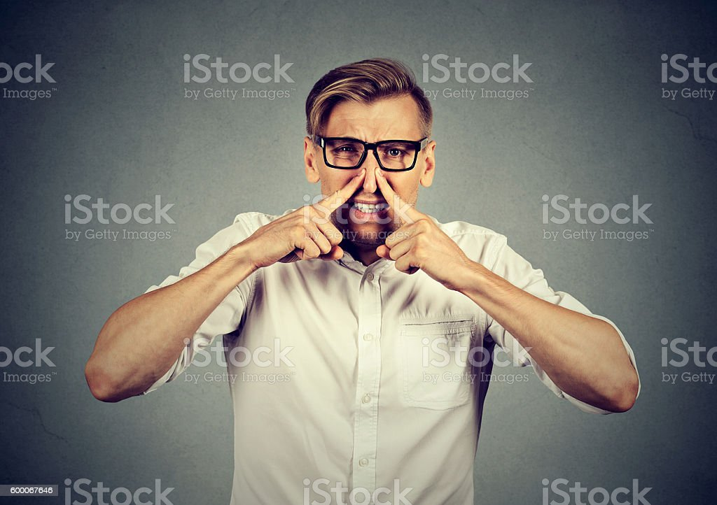 man pinches nose looks with disgust stinks bad smell stock photo