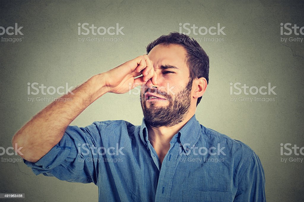 man pinches nose with fingers looks with disgust something stinks stock photo