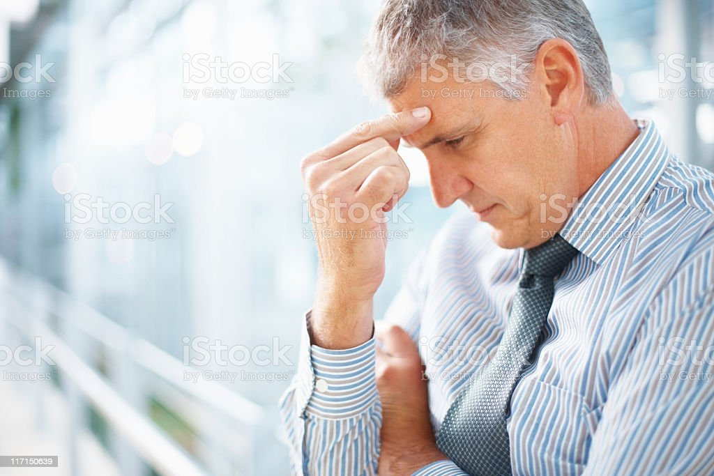 A man pinching his forehead indicating a headache royalty-free stock photo