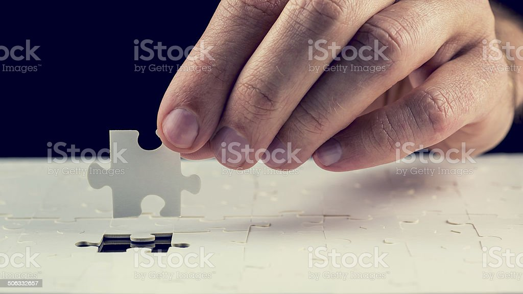 Man placing the last piece in  jigsaw puzzle stock photo