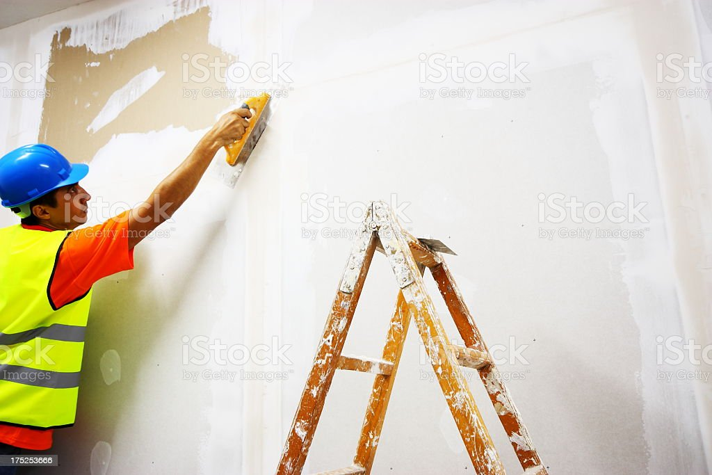 Man plastering wall next to wooden step ladders royalty-free stock photo