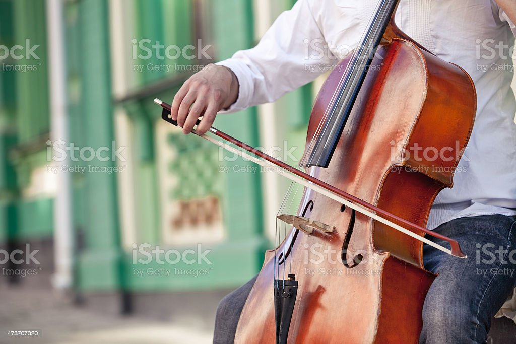 Man playing a cello on a patio stock photo