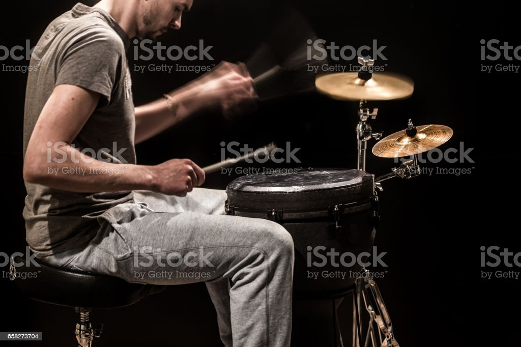 man playing a djembe drum and cymbals on a black background stock photo