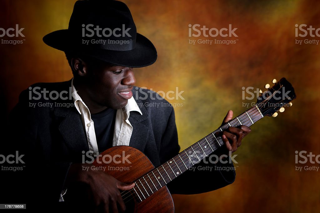 A man playing a guitar while wearing a hat and suit stock photo