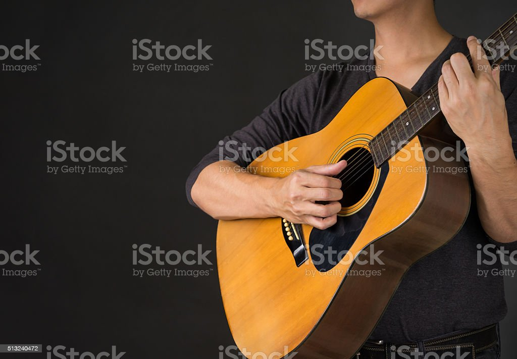 Man Playing Acoustic Guitar in Black background stock photo
