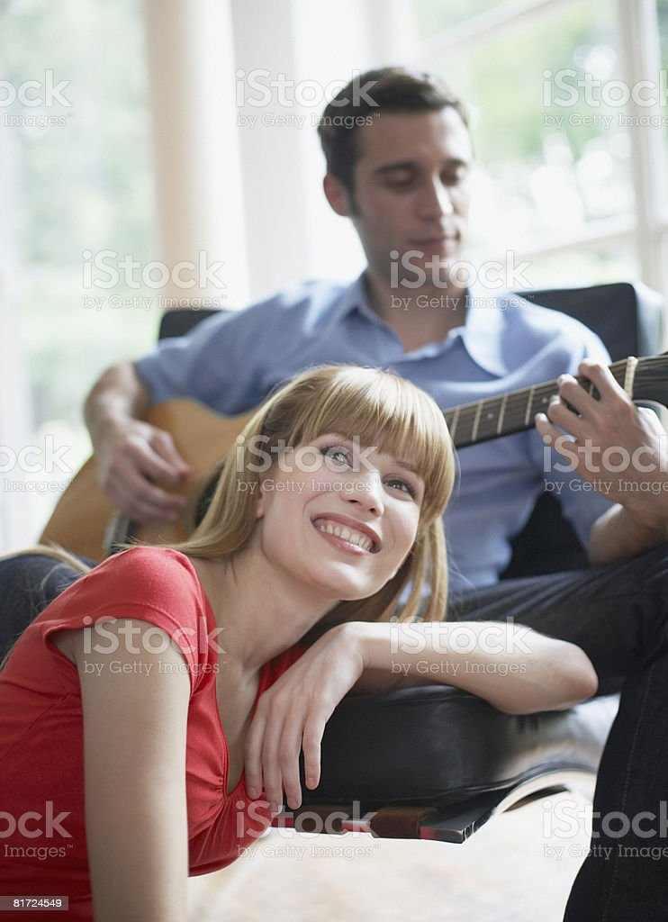 Man playing acoustic guitar indoors with woman listening royalty-free stock photo