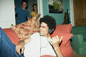 Man playing air guitar with friends watching