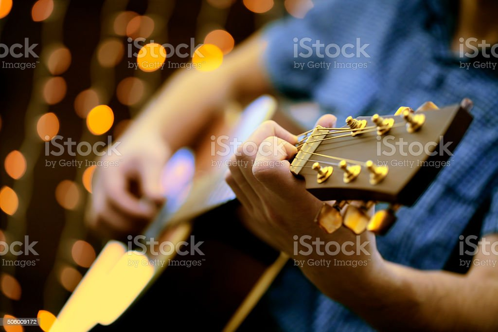 Man playing an acoustic guitar during a concert stock photo