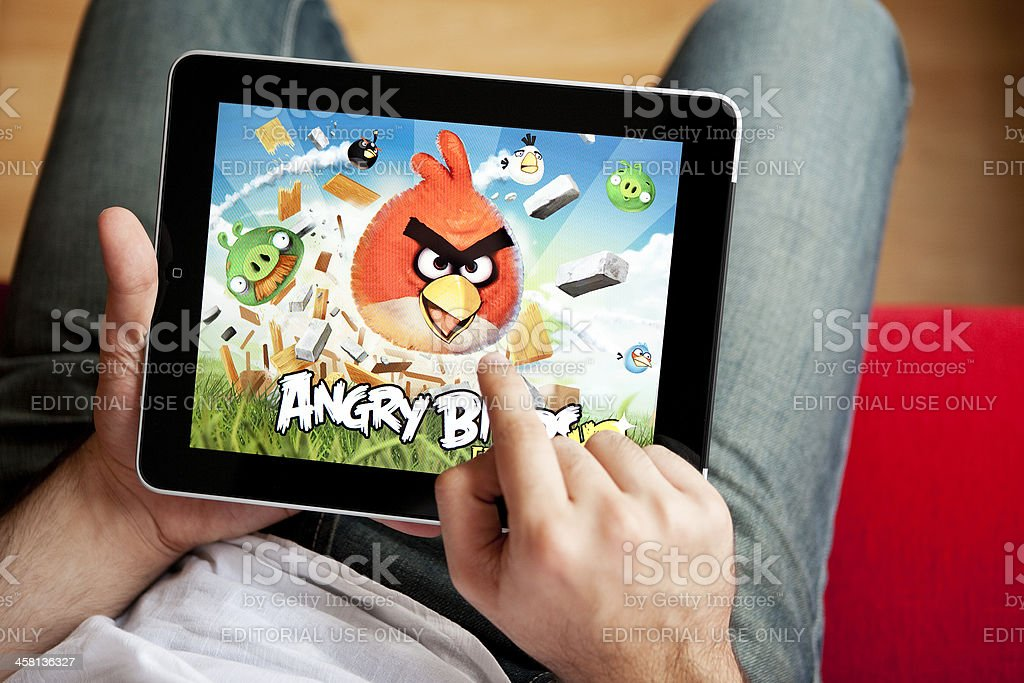 Man Playing Angry Birds on an Apple iPad royalty-free stock photo