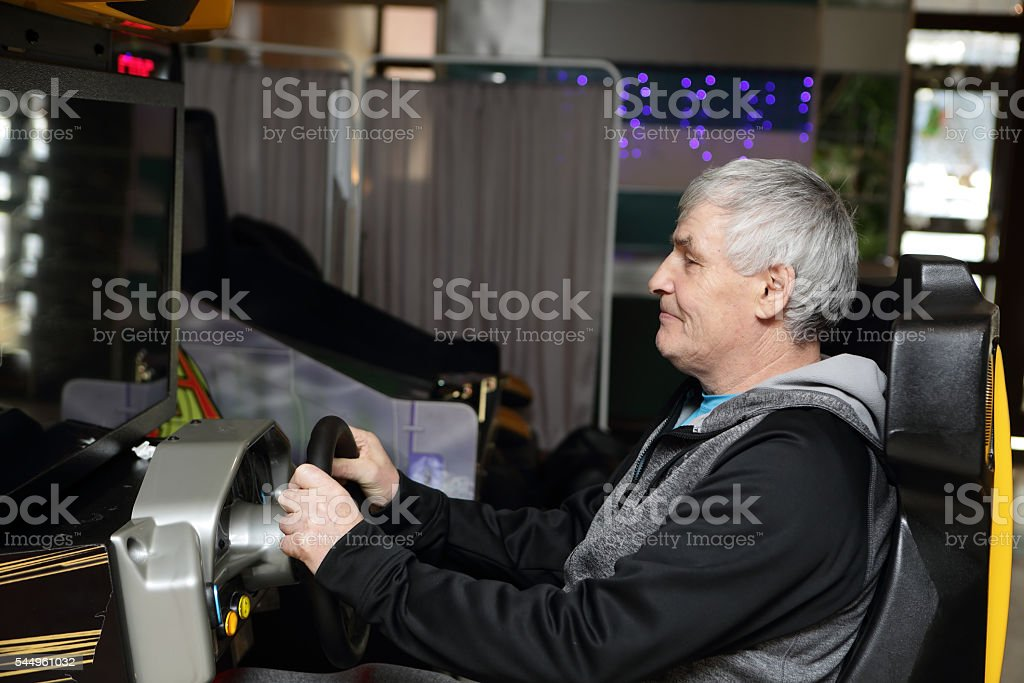 Man playing arcade game machine stock photo