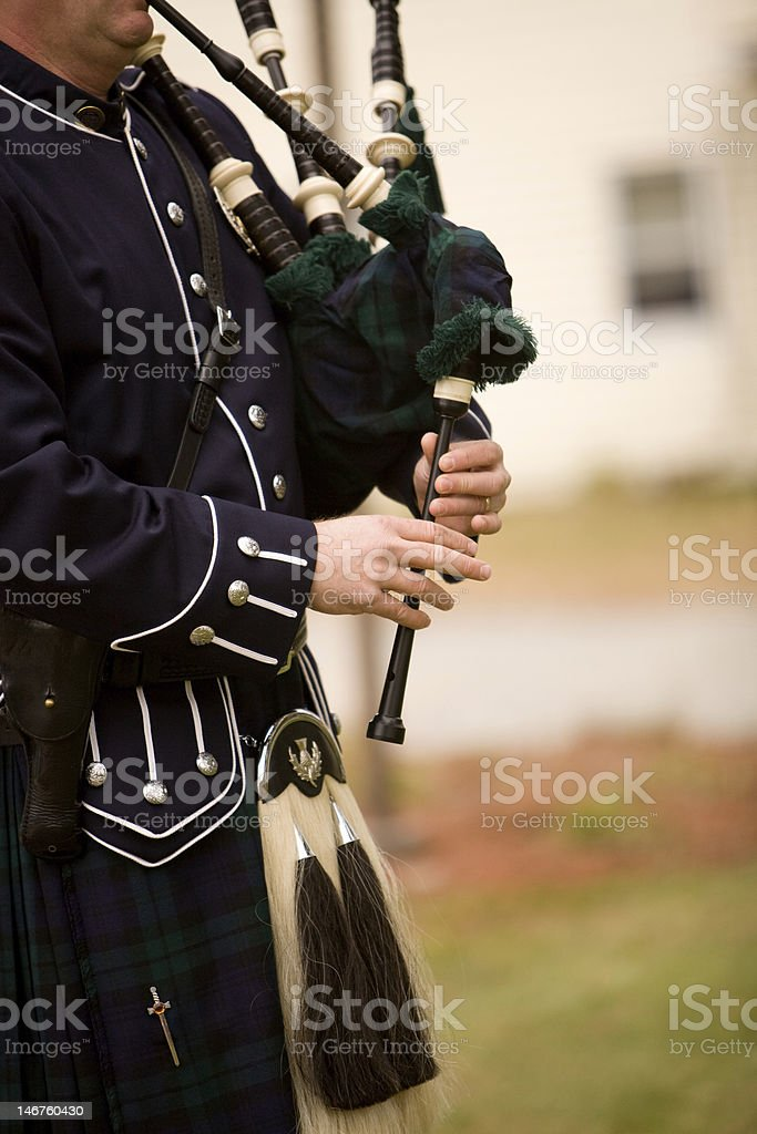 man playing bagpipes, in costume stock photo