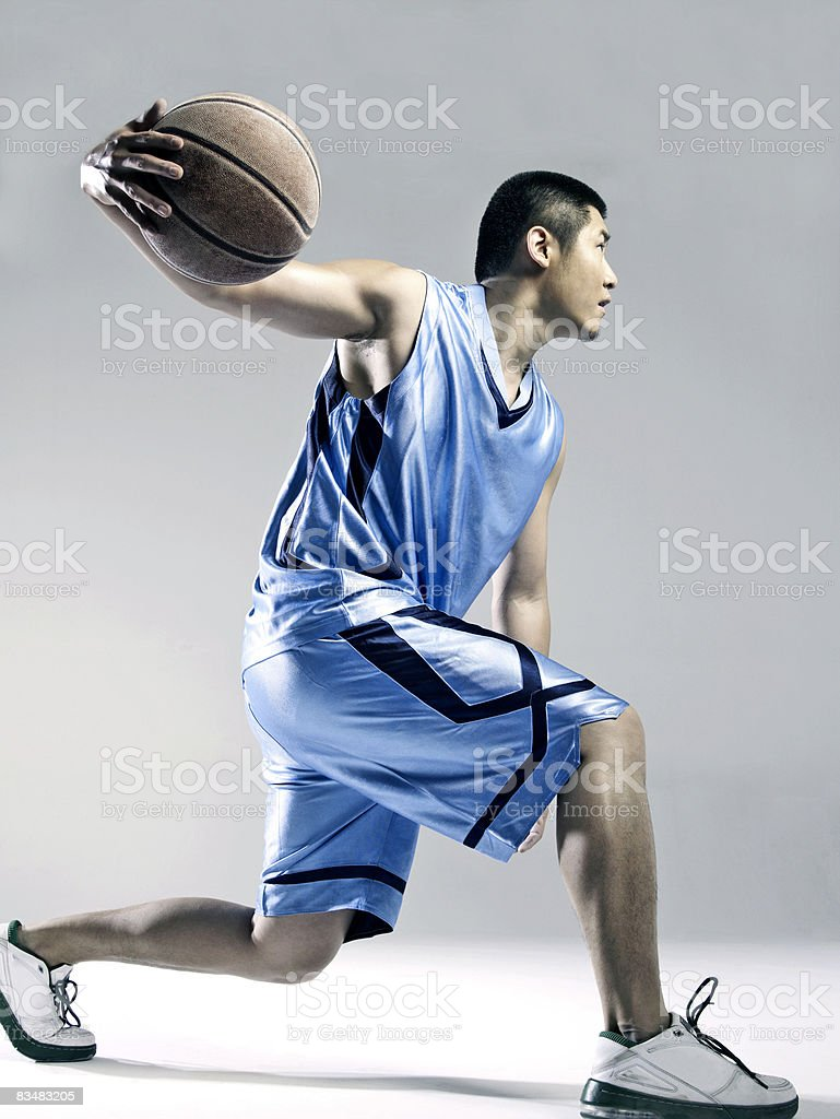 Man playing basketball, side view stock photo