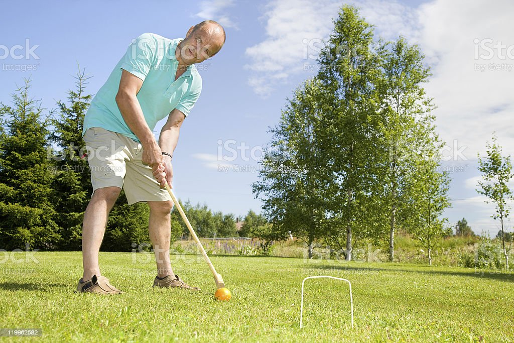 Man playing croquet on grass stock photo