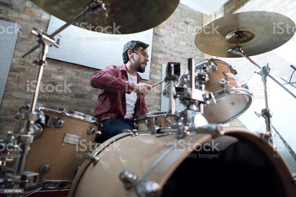 Man playing drums at a recording studio stock photo