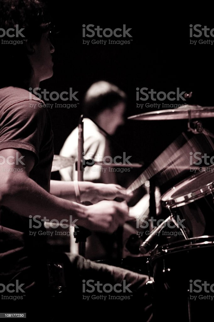 Man Playing Drums on Stage With Bassist in Background, Toned royalty-free stock photo