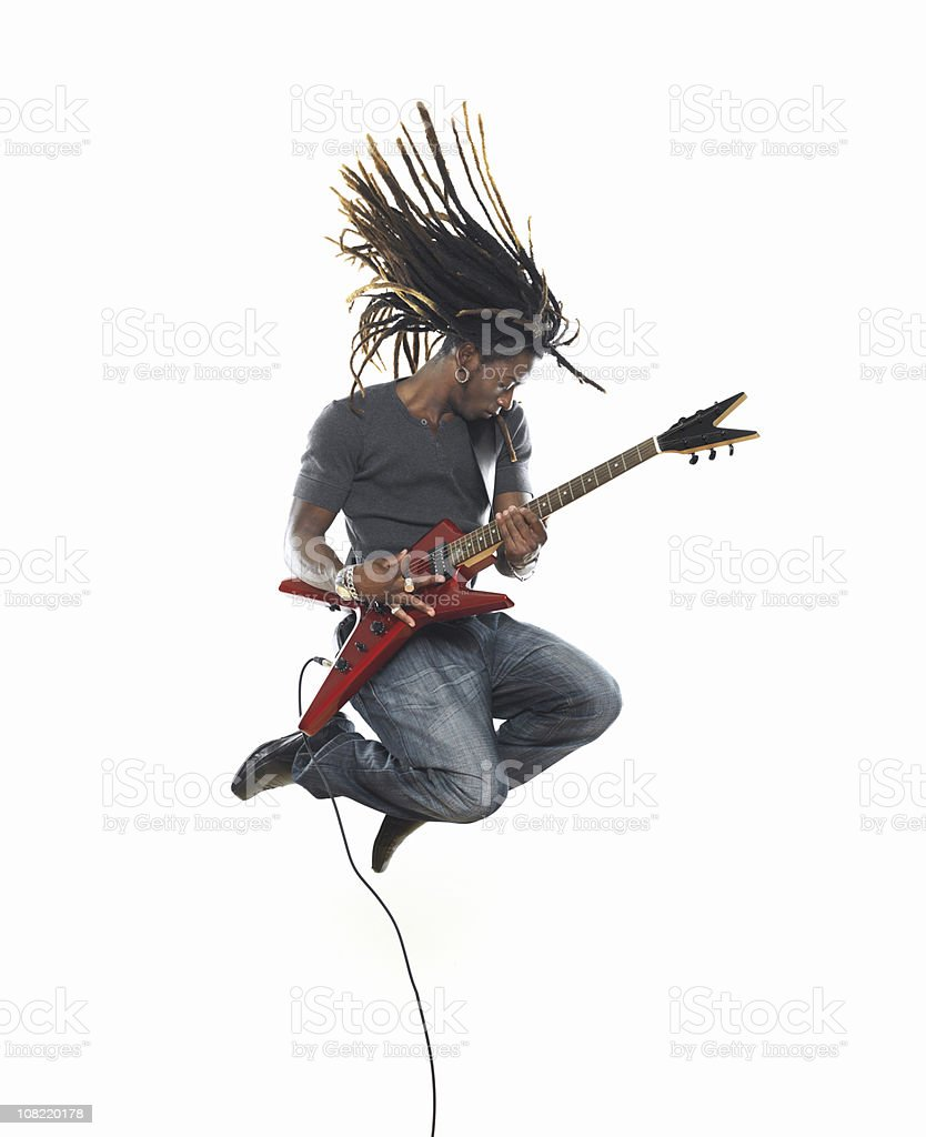 Man playing electric guitar and jumping stock photo