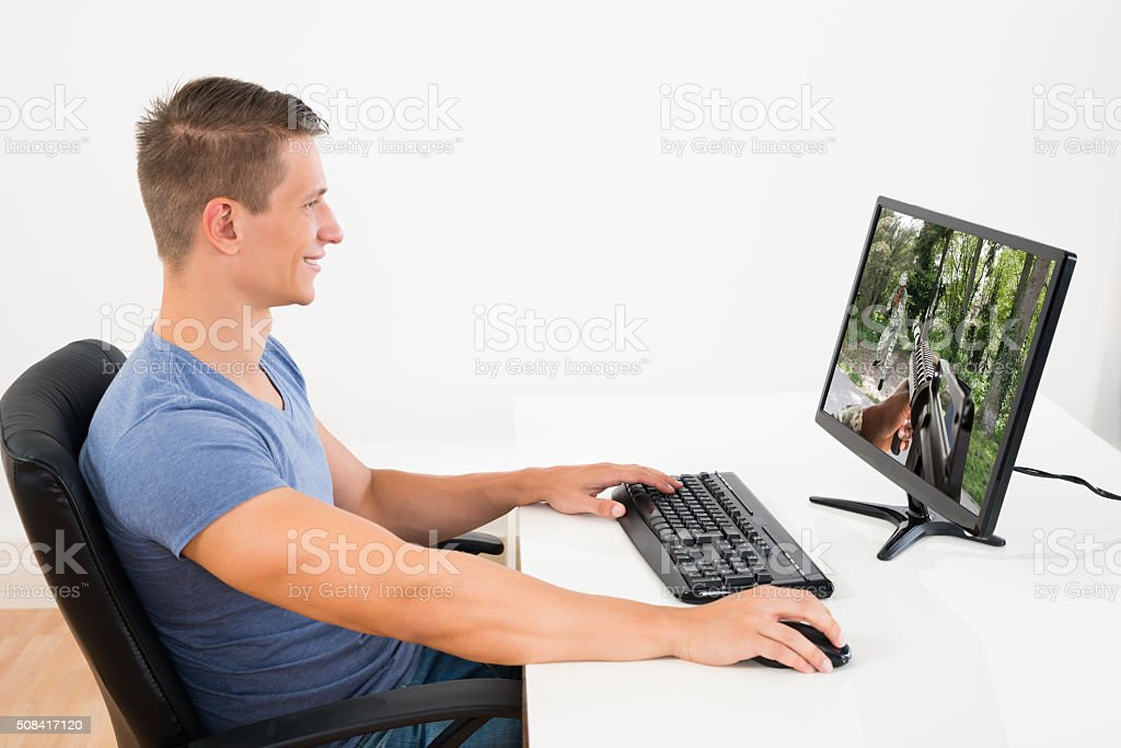 Man Playing Game On Desktop Computer stock photo