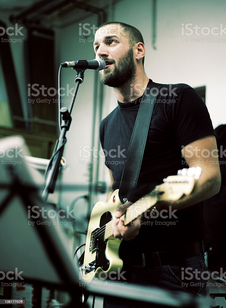 Man Playing Guitar and Singing on Stage royalty-free stock photo