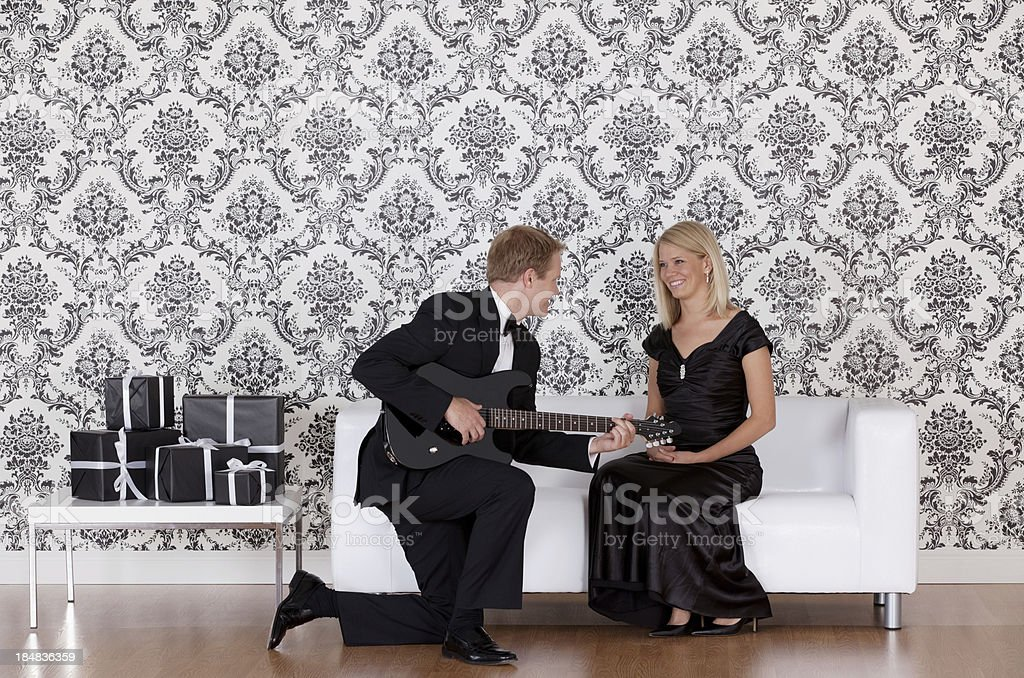 Man playing guitar for his wife royalty-free stock photo