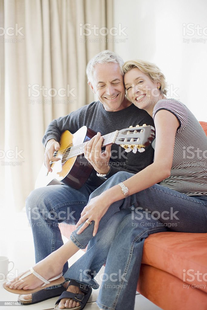 Man playing guitar for wife stock photo