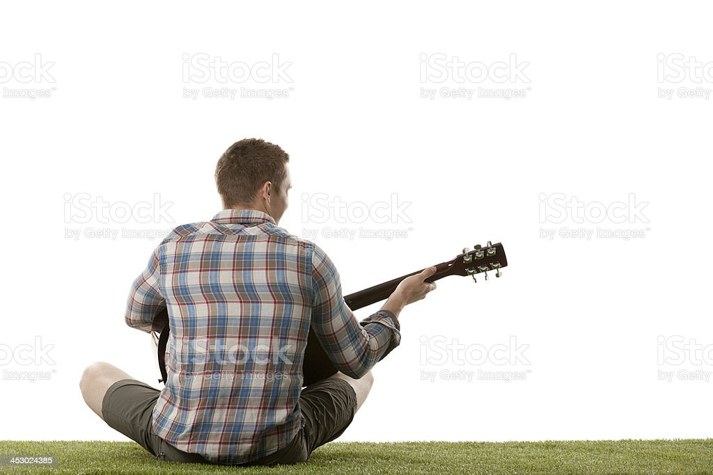 Man playing guitar in a lawn royalty-free stock photo
