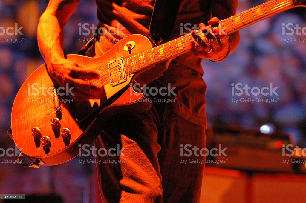 Man playing guitar on stage under orange light stock photo