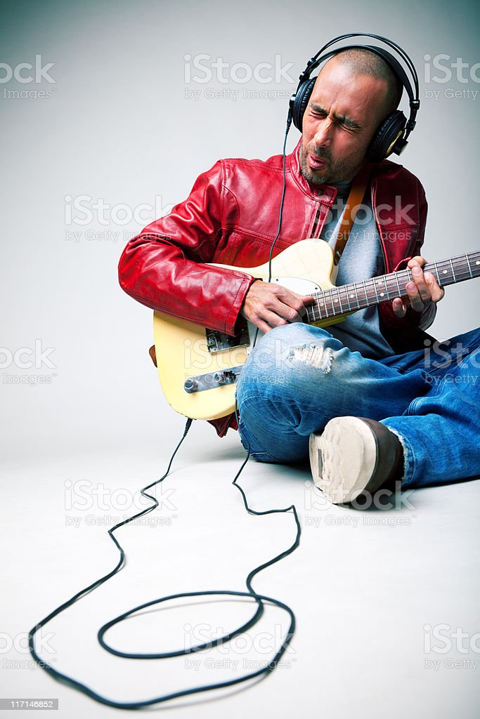 Man playing guitar with headphones royalty-free stock photo