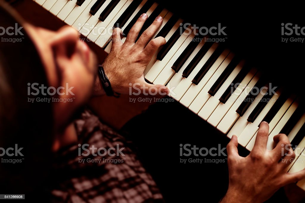 Man playing on piano on dramatic dark stage stock photo