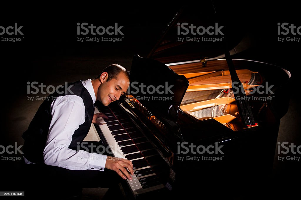Man Playing Piano with Dramatic Lighting stock photo