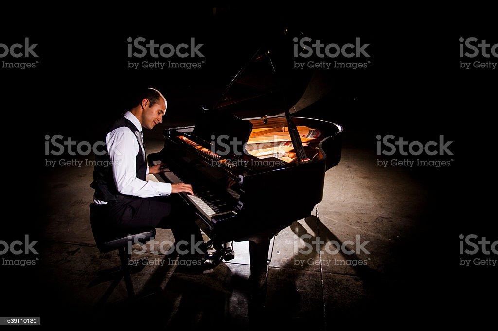 Man Playing Piano with Dramatic Lighting stock photo