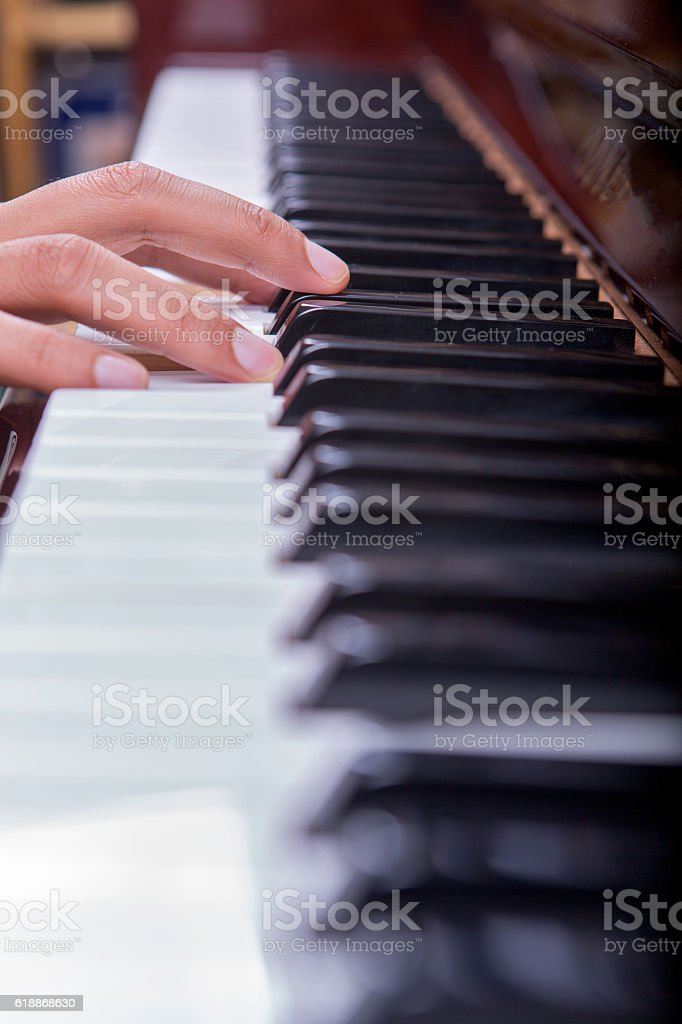 Man playing piano with one hand portrait view stock photo