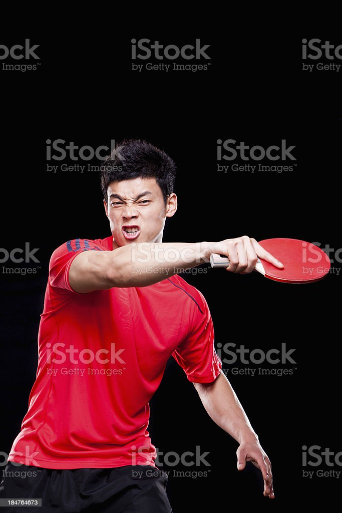 Man playing ping pong, black background stock photo