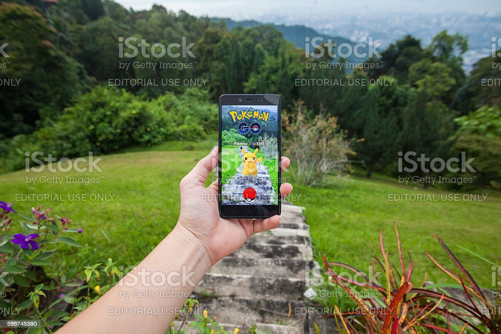 Man playing Pokemon Go with blur background stock photo