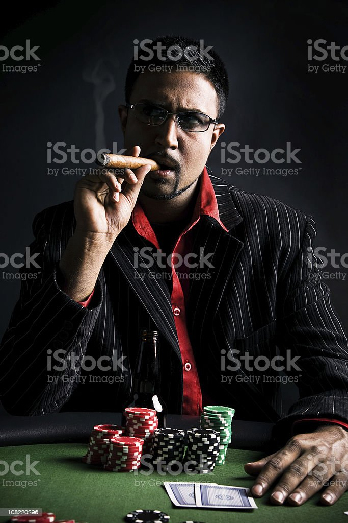 Man Playing Poker and Smoking Cigar, Low Key royalty-free stock photo