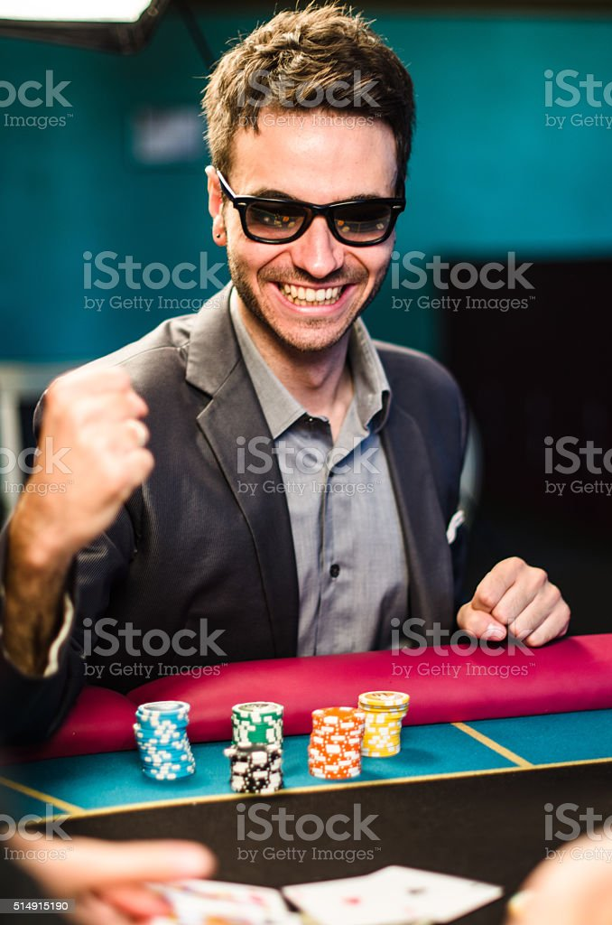 Man playing poker at casino stock photo