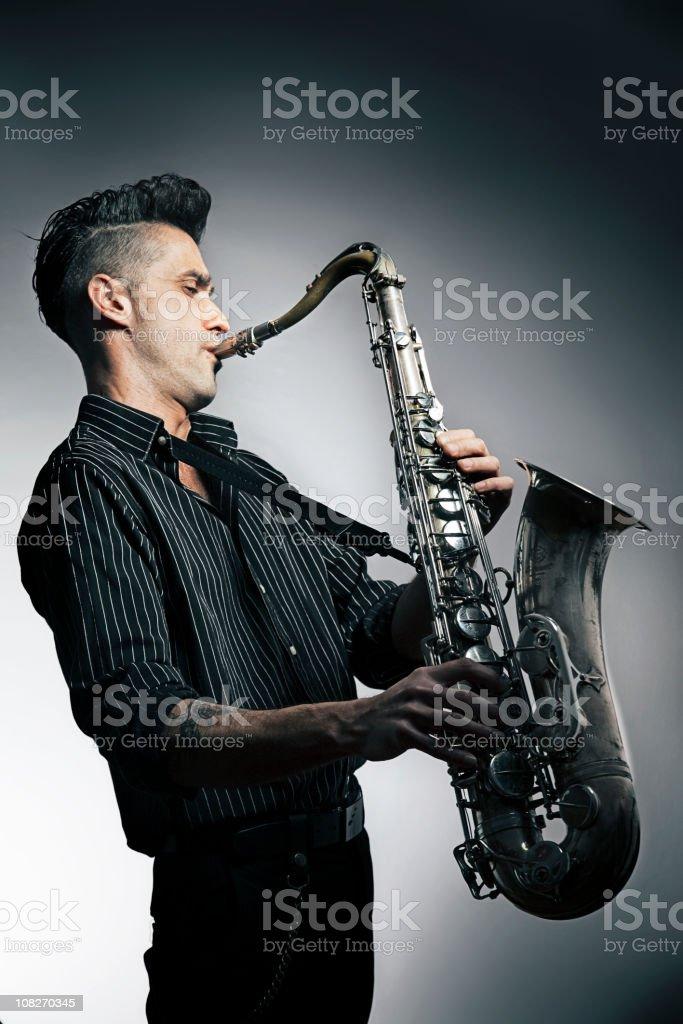 Man Playing Saxophone On Blue Background stock photo