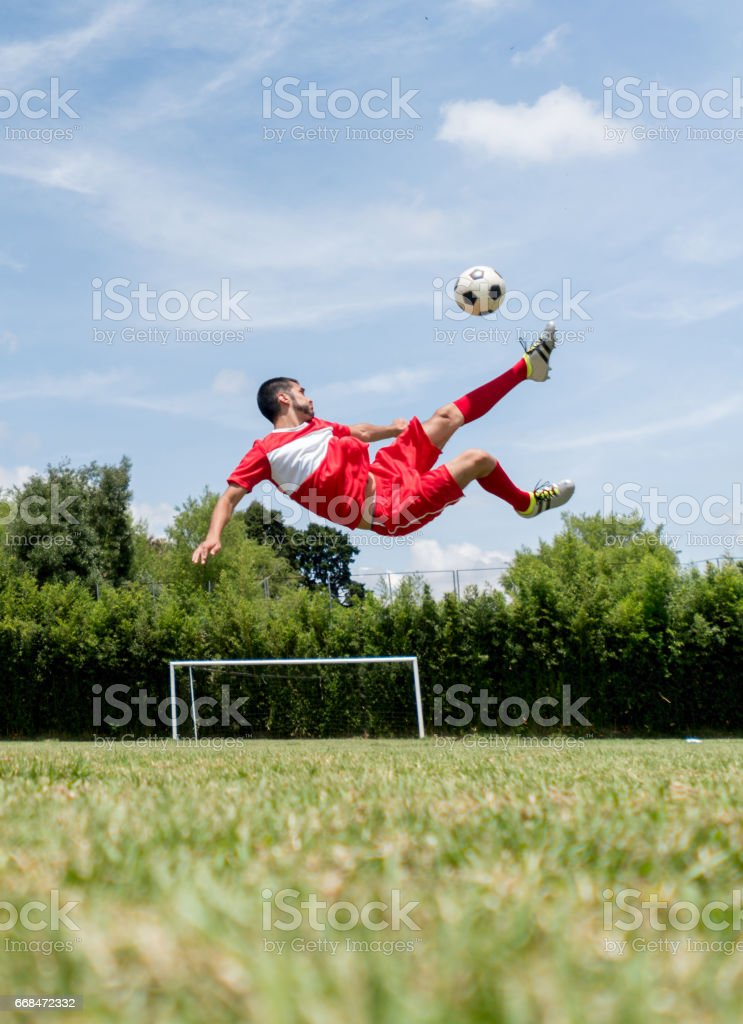 Man playing soccer and kicking the ball in the air stock photo