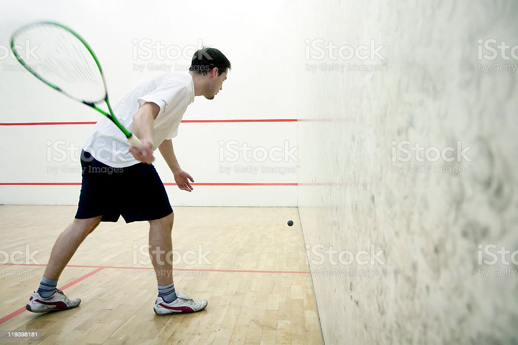 A man playing some indoor squash stock photo