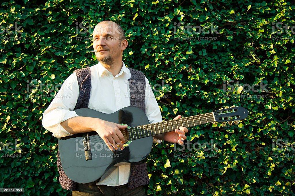 Man playing spanish guitar in green garden stock photo