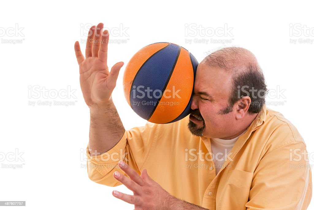 Man playing sport being hit by a basket ball stock photo