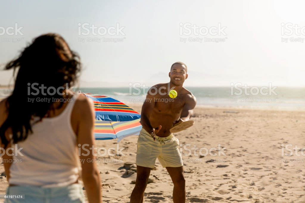 Man playing table tennis with woman at beach stock photo