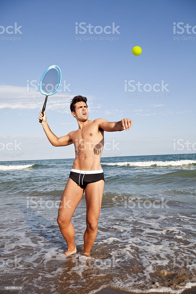 Man playing tennis on the beach royalty-free stock photo