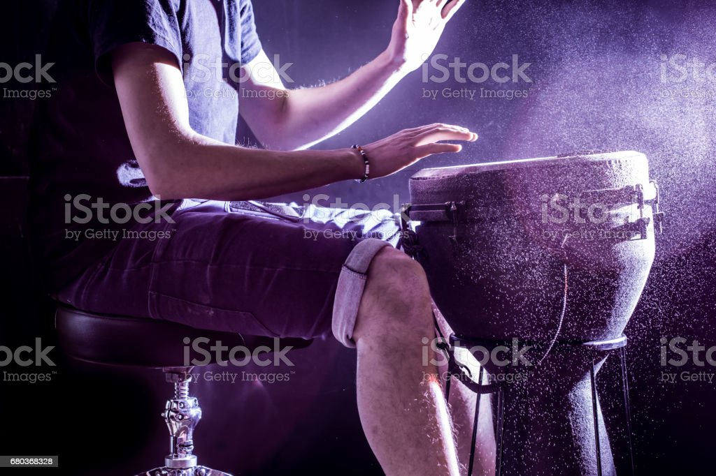 man playing the djembe, african drum, musical concept, beautiful lighting on the stage stock photo